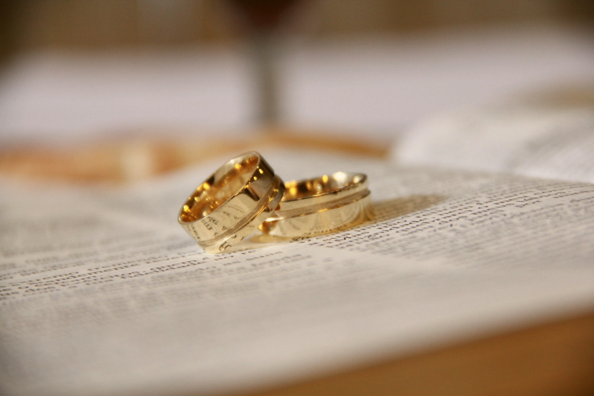 Two gold wedding rings lying together on a page of a book. Symbolising the good fortune of a Deaf Lottery Winner.